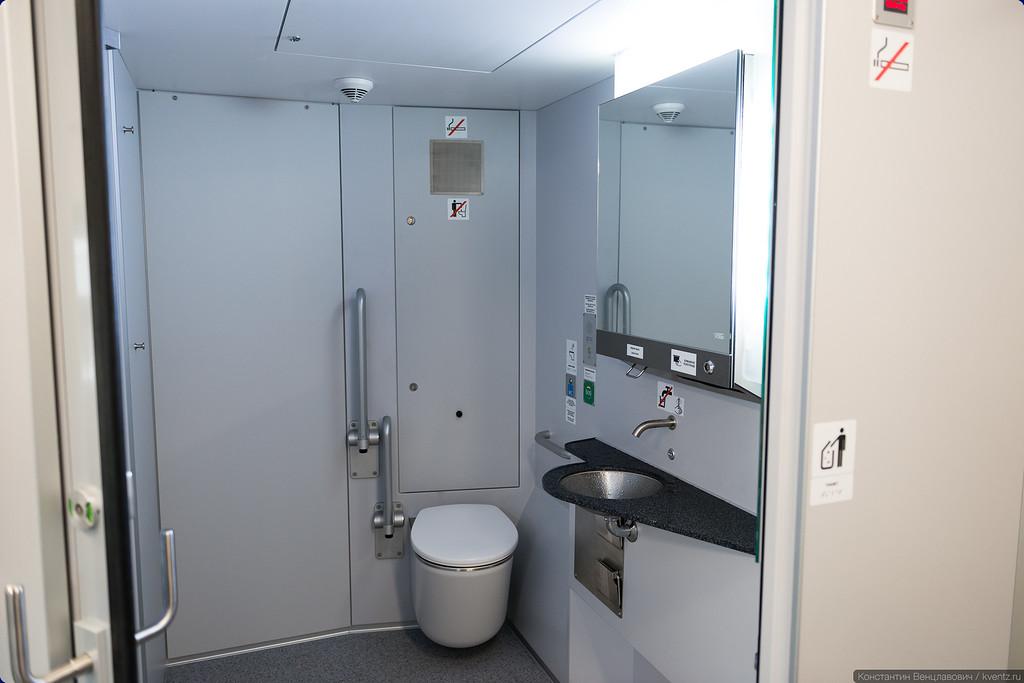 Туалет просторный, чтобы могла развернуться коляска. Дверь в туалет раздвижная, полукруглая. Справа есть два откидных сиденья. Говорят, это самые дешёвые места