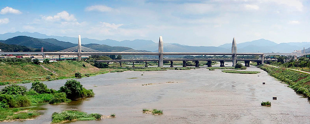 Панормама вантового моста через реку на фоне гор